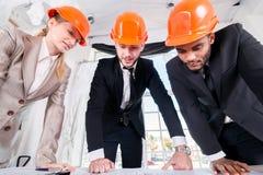 Arkitekter diskuterar projektet Mött arkitekt för tre businessmеn Royaltyfri Fotografi