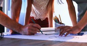 Arkitekter som arbetar på ritning på deras skrivbord 4k arkivfilmer
