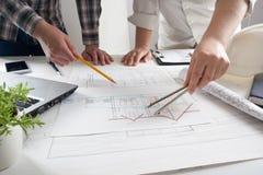Arkitekter som arbetar på ritningen, fastighetprojekt Arkitektarbetsplats - arkitektoniskt projekt, ritningar, linjal Arkivfoton