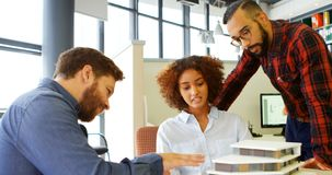 Arkitekter som diskuterar över byggnad, modellerar på skrivbordet 4k stock video