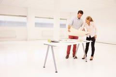 Arkitekter som planerar orienteringen av tomt kontorsutrymme royaltyfria bilder