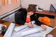 Arkitektkvinna som arbetar med ritningar royaltyfria bilder