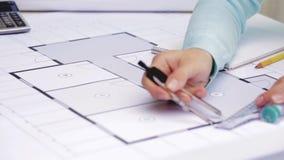 Arkitektkvinna som mäter ritningen med kompasset stock video