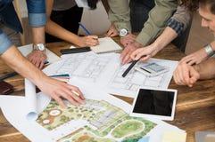 Arkitektlag som diskuterar på ritningar Arkivbilder