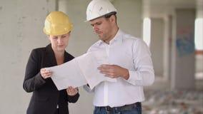 Arkitektlagman och kvinna som diskuterar om byggnadsplanet för konstruktion på jobbplatsen arkivfilmer