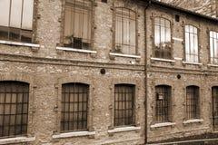 arkitektonisk detalj av de stora fönstren av ett gammalt industriellt b Arkivfoto