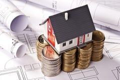 Arkitektonisk modell på buntar av mynt Royaltyfria Foton