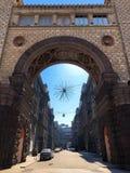 Arkitektonisk stor forntida tappning stenar den härliga bågen och en smal stadsgata arkivfoton