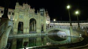 Arkitektoniska detaljer av byggnaderna och brdgesna, på natten, av Plaza de Espana i Seville, Spanien royaltyfria bilder