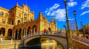Arkitektoniska detaljer av byggnaderna och brdgesna av Plaza de Espana i Seville, Spanien, med turister arkivbild