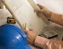 Arkitektoniska plan av konstruktionstekniker-arkitekten som granskar plan med metern, hjälmen, räknemaskinen och blyertspennan arkivfoto