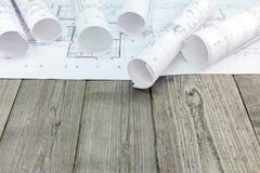 Arkitektoniska ritningar med golvplan på grå träbackgrou Fotografering för Bildbyråer