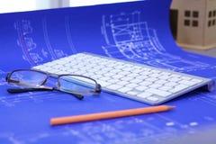 Arkitektoniska ritningar och ritningrullar och instrument för en teckning på worktablen royaltyfria foton
