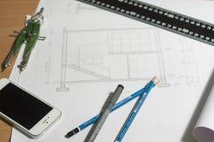 Arkitektoniska ritningar och ritningrullar och instrument för en teckning Royaltyfri Foto