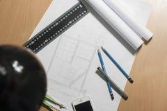 Arkitektoniska ritningar och ritningrullar och instrument för en teckning Arkivbild