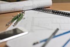 Arkitektoniska ritningar och ritningrullar och instrument för en teckning Fotografering för Bildbyråer