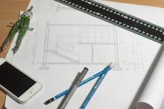 Arkitektoniska ritningar och ritningrullar och instrument för en teckning Royaltyfria Bilder