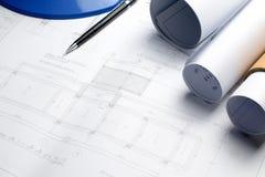 Arkitektoniska ritningar och ritningrullar och instrument för en teckning på worktablen royaltyfria bilder