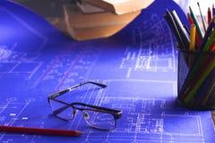 Arkitektoniska ritningar och ritningrullar och instrument för en teckning på worktablen arkivbilder