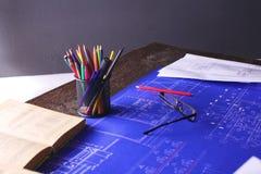 Arkitektoniska ritningar och ritningrullar och instrument för en teckning på worktablen royaltyfri fotografi