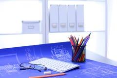 Arkitektoniska ritningar och ritningrullar och instrument för en teckning på worktablen royaltyfri foto