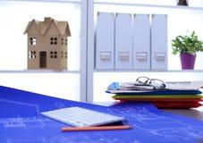 Arkitektoniska ritningar och ritningrullar och instrument för en teckning på worktablen arkivbild