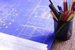 Arkitektoniska ritningar och ritningrullar och instrument för en teckning på worktablen arkivfoto