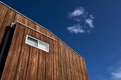 Arkitektoniska särdrag av ett modernt hus med wood cladding och ett fönster mot en blå himmel med ett moln royaltyfria foton