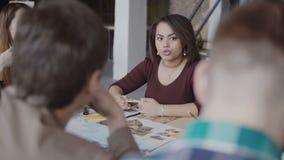Arkitektoniskt start-up företag Ungt idérikt lag som arbetar i vindkontor Afrikansk kvinna som talar med grupp människor arkivfilmer