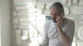 Arkitektrestauratorn talar på telefonen som står i ljust seminarium med murbrukgarneringar stock video