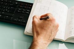 Arkitektteckningen skissar i hans anteckningsbok med en blyertspenna på en gl Royaltyfria Bilder