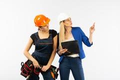 Arkitekturblick för två kvinna, i plan och att diskutera problemen av byggnad på vit bakgrund arkivfoton