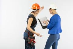 Arkitekturblick för två kvinna, i plan och att diskutera problemen av byggnad på vit bakgrund arkivbild