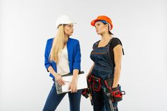 Arkitekturblick för två kvinna, i plan och att diskutera problemen av byggnad på vit bakgrund royaltyfri foto