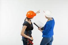 Arkitekturblick för två kvinna, i plan och att diskutera problemen av byggnad på vit bakgrund fotografering för bildbyråer