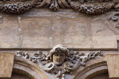 Arkitekturdetalj med det mänskliga huvudet och blommor Arkivbilder
