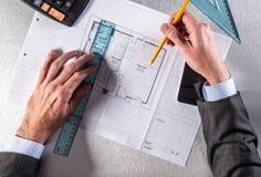 Arkitekturprofessionelln räcker danandemätningar på bostads- blått tryck Royaltyfri Foto