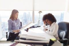 ArkitektWomen Colleagues With ritningar som undersöker att inhysa som är pro- Arkivbild