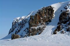 Arktic. Cliffs protruding from the snow. Stock Image