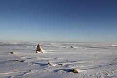 Arktische Landschaft des Winters mit einem kleinen Inukshuk Lizenzfreie Stockbilder