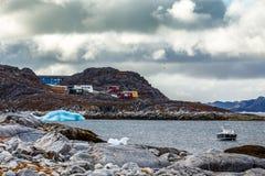 Arktische Steinküste, Motorboot und blauer Eisberg, die in das b schwimmen Stockbild