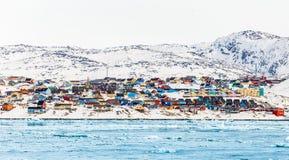 Arktisk stadspanorama med färgrika inuithus på den steniga hilen Royaltyfri Fotografi