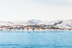 Arktisk stadspanorama med färgrika inuithus på den steniga hilen Arkivfoton