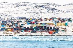 Arktisk stadspanorama med färgrika inuithus på den steniga hilen Arkivfoto
