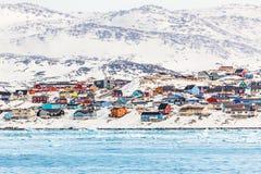 Arktisk stadspanorama med färgrika inuithus på den steniga hilen Fotografering för Bildbyråer