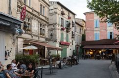People sitting at a cafe in Place du Forum, Arles, Provence, France. Arles, France - June 26, 2017: People sitting at a cafe in Place du Forum, Arles, Provence Royalty Free Stock Photo