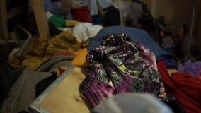 Armário bagunçado com as pilhas da roupa velha que encontra-se no assoalho e em uma escadaria vídeos de arquivo