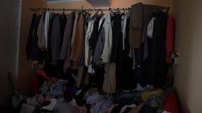 Armário caótico com os montões da roupa de segunda mão que encontra-se no assoalho desarrumado video estoque