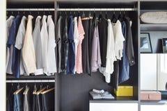 Armário com fileira dos panos que penduram no vestuário preto imagens de stock