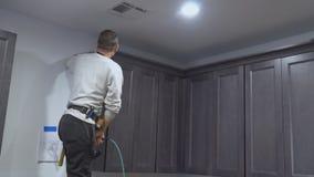 Armário de cozinha do trabalhador preto que instala os armários moldando da coroa da cozinha que quadro a guarnição vídeos de arquivo